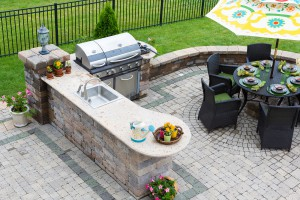 High angle view of a stylish outdoor kitchen gas barbecue and dining table set for entertaining guests with formal place settings and flowers on a paved patio
